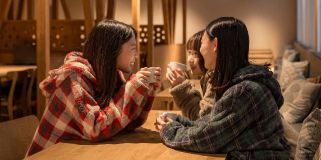 コーヒーを飲みながら談笑する 女性3人